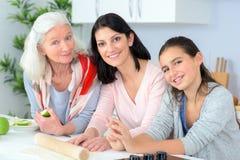 Drei Generationsfrauen, die zusammen backen stockfotos