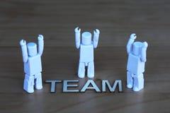 Drei generische Zahlen, die als Team feiern Lizenzfreie Stockfotos