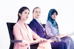 Drei Geschäftsfrau, die im Konferenzgeschäftstraining sitzt stockbild