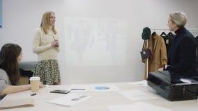 Drei Geschäftsfrauen besprechen ihr Kleidungsgeschäft in einem Raum durch Tabelle stock video