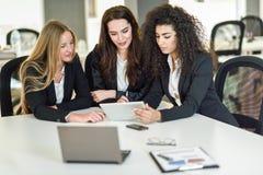 Drei Geschäftsfrauen, die in einem modernen Büro zusammenarbeiten Stockfotografie