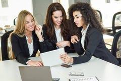Drei Geschäftsfrauen, die in einem modernen Büro zusammenarbeiten Lizenzfreies Stockbild
