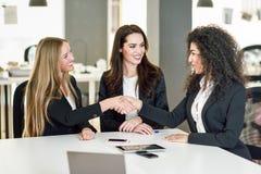Drei Geschäftsfrauen, die Hände in einem modernen Büro rütteln Stockbild