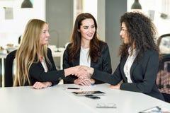 Drei Geschäftsfrauen, die Hände in einem modernen Büro rütteln Stockfotografie