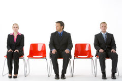 Drei Geschäftsleute, die auf roten Plastiksitzen sitzen Lizenzfreies Stockbild