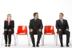 Drei Geschäftsleute, die auf roten Plastiksitzen sitzen Lizenzfreie Stockbilder
