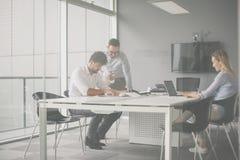 Drei Geschäftsleute, die im Büro arbeiten Kollege zwei, der c hat stockbild