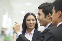 Drei Geschäftsleute, die Wand, Arm angehoben sprechen und betrachten Lizenzfreie Stockfotos