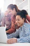 Drei Geschäftsleute um einen Laptop stockbild