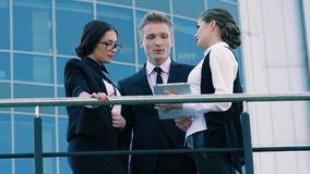 Drei Geschäftsleute: zwei Frauen und Mann, die über ihre zukünftige Zusammenarbeit sprechen stock footage