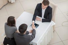 Drei Geschäftsmänner, die Hände am Tisch rütteln Beschneidungspfad eingeschlossen Stockbild
