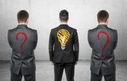 Drei Geschäftsmänner, die mit Zeichnung der Glühlampe und der Fragezeichen auf seinem zurück stehen Lizenzfreie Stockfotografie