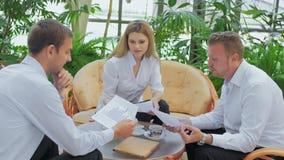 Drei Geschäftsmänner sitzen an einem Tisch und besprechen den Arbeitsplan stock video footage