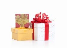 Drei Geschenkboxen, die mit farbigen Satinbändern gebunden werden, beugen auf Weiß Lizenzfreie Stockfotografie