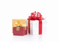 Drei Geschenkboxen, die mit farbigen Satinbändern gebunden werden, beugen auf Weiß Lizenzfreie Stockfotos