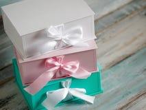 Drei Geschenkboxen, Weiß, Rosa und Türkis Draufsicht diagonal auf einem hölzernen Hintergrund Geschenke für Ihre Freundin Lizenzfreies Stockfoto