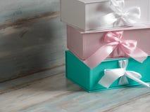 Drei Geschenkboxen, Weiß, Rosa und Türkis Hölzerner Hintergrund Stockbild