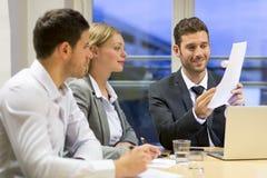 Drei Geschäftsvölker, die im Konferenzzimmer zusammenarbeiten Lizenzfreie Stockfotos