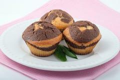 Drei geschmackvolle Muffins auf einer weißen Platte Stockbild