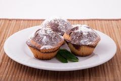 Drei geschmackvolle Muffins auf einer weißen Platte Lizenzfreies Stockfoto