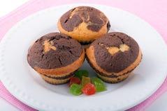 Drei geschmackvolle Muffins auf einer weißen Platte Stockfotos