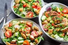 Drei gesunde Salate mit Gemüse und Huhn Stockbilder