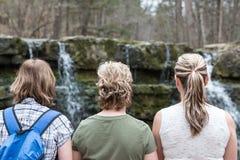 Drei gewachsene Schwestern, die zusammen durch Wasserfall sitzen Lizenzfreies Stockbild