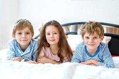 Drei glückliche Kinder in den Pyjamas Pyjamapartei feiernd Vorschule und Schuljungen und -mädchen, die Spaß zusammen haben Kinder stockfotografie