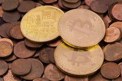 Drei glänzendes Bitcoins, das auf einen Stapel von alten Kupfermünzen des Eurocents legt Lizenzfreies Stockfoto