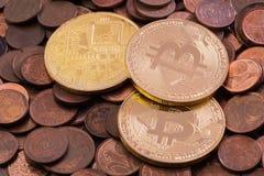 Drei glänzendes Bitcoins, das auf einen Stapel von Kupfermünzen des Eurocents legt Lizenzfreies Stockbild