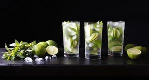 Drei Gläser Cocktail mojito Limonade auf der Bar Parteicocktail Kalk, Eis und Minze auf dem Tisch Schwarzer Hintergrund Stockfotografie