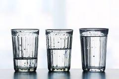 Drei Gläser mit verschiedenen Niveaus des Wassers Stockbild