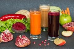 Drei Gläser unterschiedlicher frischer Saft Rote Rübe, Karotte und Apfelsäfte auf grauem hölzernem Hintergrund lizenzfreies stockfoto