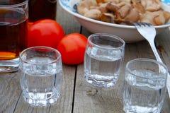 Drei Gläser Wodka auf einem Holztisch Lizenzfreies Stockfoto