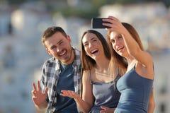 Drei glückliche Freunde, die selfies in den Stadtstadtränden nehmen stockbilder