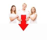 Drei glückliche Jugendliche, die einen roten Pfeil auf Weiß halten Stockfotos