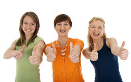 Drei glückliche junge Frauen, die Daumen aufgeben Stockfotografie