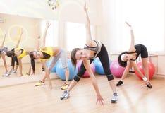 Drei glückliche kaukasische weibliche Athleten im guten Sitz, der das Ausdehnen von Übungen hat stockbild