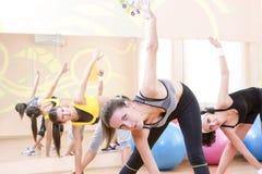 Drei glückliche kaukasische weibliche Athleten im guten Sitz, der das Ausdehnen von Übungen hat stockfoto