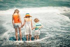 Drei glückliche Kinder, die auf Strand spielen Stockfotos