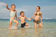 Drei glückliche Kinder, die auf Strand spielen Lizenzfreies Stockbild