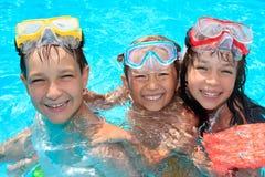 Drei glückliche Kinder im Pool Stockfotografie