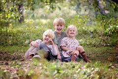 Drei glückliche Kleinkinder, die draußen lachen stockfotos