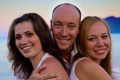 Drei glückliche Leute auf dem Strandsonnenuntergang Stockfotos