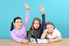 Drei glückliche Mädchen, die ihre Schulearbeit erledigen Stockfoto