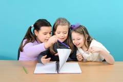 Drei glückliche Mädchen, die ihre Schulearbeit erledigen Lizenzfreies Stockbild