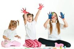 Drei glückliche Mädchen, die mit Fingerfarben spielen Stockfotos