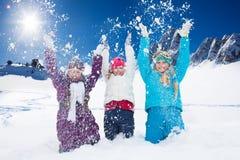 Drei glückliche Mädchen, die Spaß mit Schnee haben Stockbilder