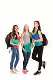 Drei glückliche Studenten, die zusammen mit Spaß stehen Lizenzfreie Stockfotos