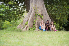 Drei glückliche weibliche Freunde, die nahe großem Baum sitzen Lizenzfreies Stockbild